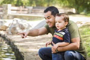 Happy Hispanic Father Points with Mixed Race Son at the Park Pon