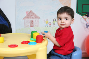 Toddler playing with colorful dough toy